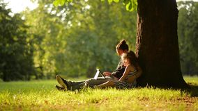 Two girls using tablet in a beautiful park, a warm summer day. Sisters look photos on the tablet, sitting under a tree stock video footage