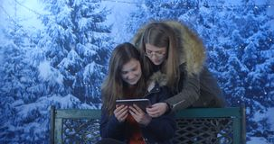 Two girls using their mobile phones. In winter time stock video footage