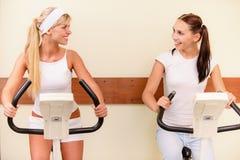 Two girls on velosimulators Stock Images