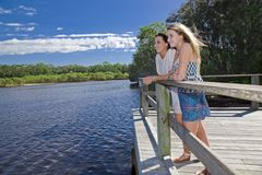 Two girls on viewing platform by the creek Stock Photos