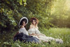 Two girls in vintage clothes and hats. Blonde and brunette royalty free stock images
