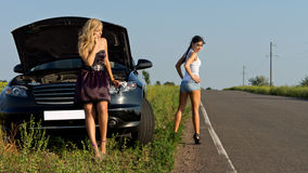 Two girls wait for the help on the road Royalty Free Stock Photography