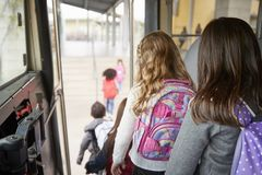 Two girls waiting behind their friends to get off school bus royalty free stock photography