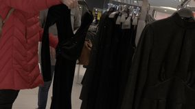 Two girls walk around the boutique in the shopping center and choose an evening dress. Slow motion. Close up stock video
