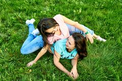 Two girls walk through the city. Two young happy girls lie on green grass Stock Images