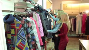 Two girls walk in a clothing store, they look at clothes and try it on. Portrait of two young girls in a fashion clothing store. Shopping on site stock footage