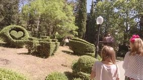 Two girls walk through the summer garden and shoot around camera. HD stock footage