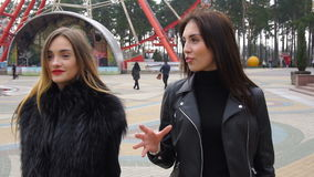 Two girls walk and talks around the city stock video footage