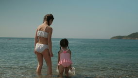 Two girls walk on water by sea on summer day outdoors. Children gradually get used to cool turquoise water, slowly leaving picturesque shore. Little sisters stock video footage