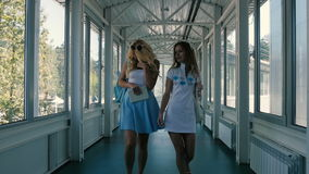Two girls walking across the long corridor. One of the girl hold a tablet in the hand. The girls are smiling, laughing and happy stock video footage