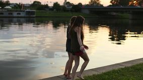 Two  girls walking along the city waterfront during sunset. Two teenage girls walking along the city waterfront during sunset stock video