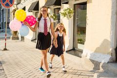 Two girls are walking along the street with colorful balloons. Children in school uniform, glasses, backpack.  Stock Photos