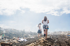 Two girls walking around garbage mountain Stock Photos