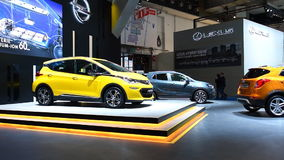 Two girls walking away from the Opel Ampera-e compact full electric car. During the 2017 European Motor Show Brussels stock footage