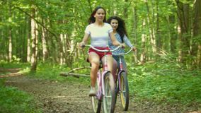 Two girls walking with bicycles in the green forest, summer day. Telephoto shot stock video