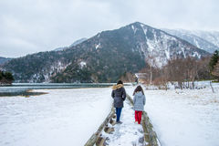 Two Girls Walking on Boardwalk by Lake in Snow Royalty Free Stock Photos