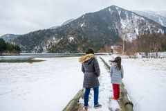 Two Girls Walking on Boardwalk by Lake in Snow and Wind Royalty Free Stock Photos