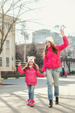 Two girls walking  in the city. Royalty Free Stock Photo