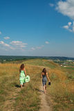 Two girls walking down the hill. Two barefooted girls walking down the hill along the path stock images