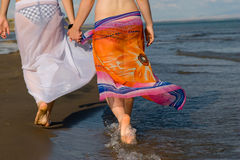 Two girls walking on the edge of sea. Two girls walking on the edge of the sea Stock Photos
