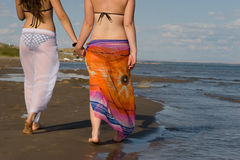 Two girls walking on the edge of the sea. Two girls walking on the edge Royalty Free Stock Image