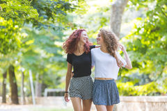 Two girls walking embraced at park. Royalty Free Stock Image