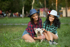Two girls walking with his dog. cowboy hat and Stock Photography