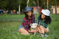 Two girls walking with his dog. cowboy hat and Royalty Free Stock Photography
