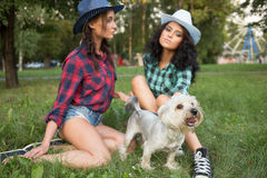 Two girls walking with his dog. cowboy hat and Stock Photos