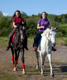 Two girls walking on horseback Stock Photography