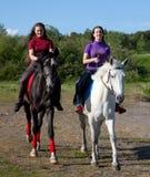 Two girls walking on horseback stock photography