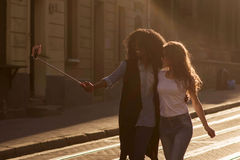 Two girls walking and making selfie. Beautiful city and sunny weather. Stock Photo