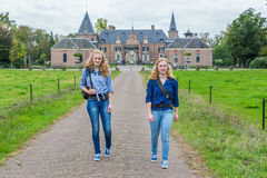 Two girls walking on road away from castle Stock Photos