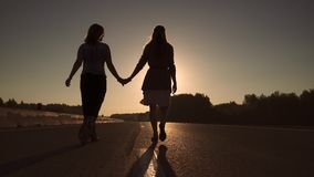 Two girls are walking on the road at dawn. Girls hippie dancing at dawn. two young girls carelessly having fun stock video footage