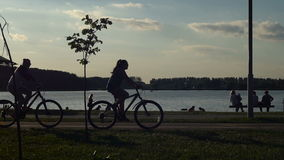 Two girls walking on summer evening embankment. Cyclist rides along the bike path. Beautiful evening sunset sky stock video footage