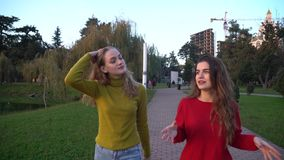Two girls walking and talking at park in Batumi.  stock video footage