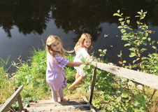 Two girls walking to the river. Young kids - barefoot girls walking to the water of river on wooden stairs Stock Image