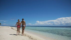 Two girls walking on a tropical beach stock footage