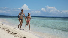 Two girls walking on a tropical beach. Happy sisters having fun walking on the tropical beach.Two young girls in swimsuit walking on tropical beach holding hands stock footage