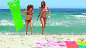 Two girls walking up from the water at the beach. And lying on their towels stock footage