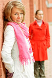 Two girls at wall. Girl in white short coat leans against wall, and on background its girlfriend in red coat Stock Photos