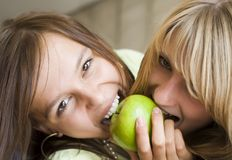 Two girls want to eat an apple stock images
