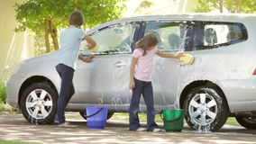 Two Girls Washing Car Together. Two girls washing car in driveway using sponge and bucket. Shot on Canon 5D MkII at 25fps stock footage