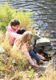 Two girls washing their feet. Young kids - barefoot girls washing their feet in water of river Stock Photos