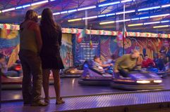 Two girls watching bumper cars Stock Photo