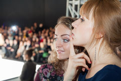 Two girls watching a fashion show. Royalty Free Stock Image