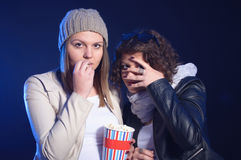 Two girls are watching horror movie in cinema Stock Photo