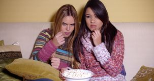 Two Girls Watching a Movie Seriously with Popcorn. Two Girls in Winter Outfits Watching a Movie at Home Seriously with a Bowl of Popcorn stock video footage