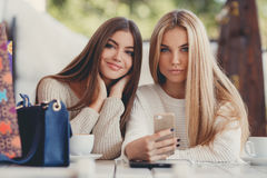 Two girls are watching photos on smartphone Stock Photo