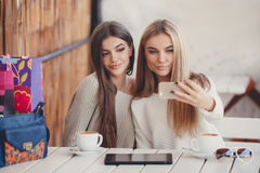 Two girls are watching photos on smartphone Royalty Free Stock Image